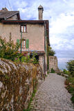 Street in Yvoire. France with stones houses and pots. It´s a vertical picture on a cloudy day Stock Photos