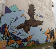 Streetart, eagle and raven. Street art in Reykjavik, an eagle attacks, a raven escapes Royalty Free Stock Photography