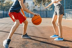 Streetball basketball game with two players, teenagers girl and boy with ball, outdoor city basketball court.  stock photo