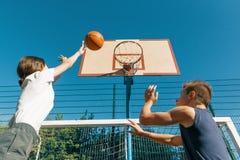 Streetball basketball game with two players, teenagers girl and boy, morning on basketball court stock photo