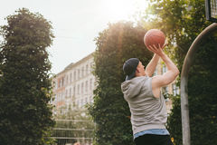 Streetball player playing on outdoor court. Image of a streetball player playing on outdoor court. Young athletic man taking jump shot on basketball court royalty free stock photography