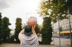 Streetball player shoots basket. Rear view shot of a young guy playing basketball on outdoor court. Streetball player shoots basket stock images