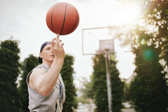 Streetball player spinning the ball. Young man balancing basketball on his finger on outdoor court. Streetball player spinning the ball. Focus on basketball Royalty Free Stock Image