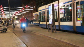 Streetcars and cyclists in Amsterdam at night. People ride on bicycles and streetcars drive by in a shopping street decorated for Christmas, leading to Dam stock video