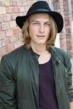 Streetkid Νεαρός άνδρας με τα μακριά ξανθά μαλλιά στο μαύρο καπέλο και το δροσερό πράσινο σακάκι Στοκ εικόνα με δικαίωμα ελεύθερης χρήσης