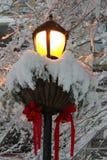 Streetlamp που διακοσμείται για τα Χριστούγεννα που καλύπτονται στο νέος-πεσμένο χιόνι Στοκ Φωτογραφίες