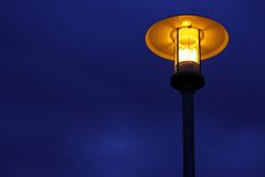 Streetlamp 1. Streetlamp in front of a cloudy sky providing warm yellow light Royalty Free Stock Photography