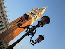 Streetlamp and building tower. An angled view of an old streetlamp in Venice, Italy, with a tall building tower in the background Royalty Free Stock Photo