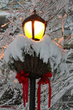Streetlamp Decorated for Christmas Covered in New-Fallen Snow. Lit streetlamp decorated with Christmas greens and red ribbons covered in freshly fallen snow Stock Photos