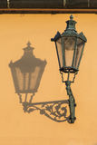 Streetlamp and shadow. Historic streetlamp casts a shadow on a yellow wall Stock Photography