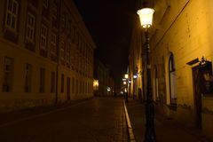 Streetlamps at night on a cobbled road stock photography