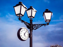 Streetlight with clock. Snow falling on a Streetlight and his watch Stock Images
