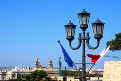 Streetlight and flags, Valletta. Maltese and EU flag on a lamppost with city buildings to the rear, Valletta, Malta, Europe Stock Images