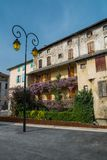 Streetlight in front of building facade. With balconies full of flowers in Saint-Girons town, France Royalty Free Stock Photos