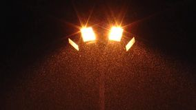 The streetlight lighting the falling snow. stock video
