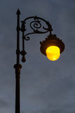 Streetlight Lit at Dawn. Streetlight urban lighting lit classic style, at dawn or dusk on a cloudy gray sky Stock Photos