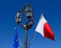 Streetlight and Maltese flag. Wrought iron streetlight with the Maltese flag and European Union flag in Castille Square, Valletta, Malta, Europe Stock Photos