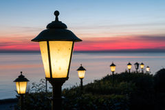 Streetlights along Dutch boulevard with beautiful sunset over the sea Stock Image
