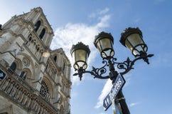 Streetlights och signage på Notre Dame Cathedral i Paris Arkivbild