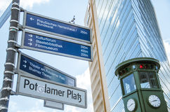 Streets of Berlin. Clock and direction signs along the Potsdamer Platz, Berlin, Germany Stock Image