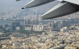 Streets and buildings underneath the wing of an aeroplane. Looking down at streets and buildings underneath the wing of an aeroplane royalty free stock image