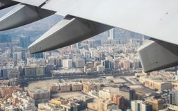 Streets and buildings underneath the wing of an aeroplane. Looking down at streets and buildings underneath the wing of an aeroplane stock photo
