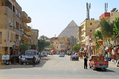 Streets of Cairo with Great pyramids of Giza. CAIRO, EGYPT - MARCH 11: Unidentified people on streets of Cairo with Great pyramids of Giza in background on Stock Image