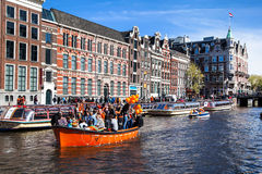 Streets and Canals of Amsterdam full of people dressed in orange celebrating King's day Royalty Free Stock Photo