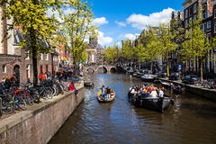 Streets and Canals of Amsterdam full of people dressed in orange celebrating King's day Royalty Free Stock Images