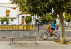 The streets of Cordoba - Spain. Cordoba/ Spain - 08/20/18 - A man biking along the river in the old town area of Cordoba - Spain stock images