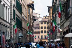 Streets of Florence, Italy. With multiple people and Italian flags on building facades Royalty Free Stock Photography