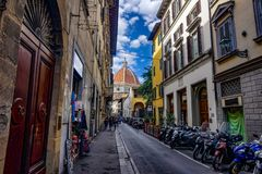 streets of Florence with motorcycles with the Florance duomo at the end royalty free stock photo