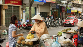 Streets of Hanoi. A fruit vendor with a customer on the street in Hanoi, Vietnam stock photo