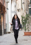 On the streets of Italy. A young beautiful dark hair woman with a handbag walking with intent in the beautiful narrow streets of Genoa, an old Italian harbor stock images