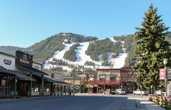 Streets of Jackson Hole with ski slopes at background Royalty Free Stock Images