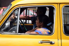 Streets of Kolkata. Lady in typical yellow taxi Stock Images