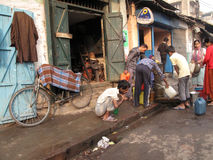 Streets of Kolkata. People filling up water in cans Stock Image