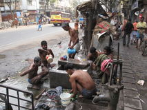 Streets of Kolkata. People wash themselves on a street Stock Image