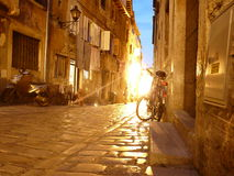 Streets of night Rovinj. Night city streets of Rovinj, Croatia. Stone roadway, bicycle, motor scooter, lantern, facades of houses, windows with shutters Royalty Free Stock Image