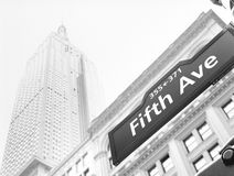 Streets of NYC. Fifth Avenue street sign against an Empire State Building Stock Image