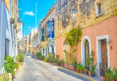 The streets in old Naxxar, Malta. The scenic street with old stone residential house with blue Maltese balconies and plants in pots along its walls, Naxxar stock photo
