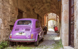 On the streets of Rhodes old town, Greece. Pink car parked on the old street in centre of Rhodes royalty free stock photo