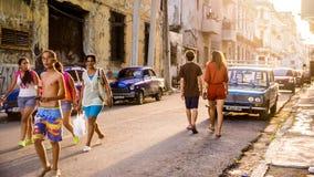 Streetscene of Cuban people walking in old Havana at sunset. Havana, Cuba on December 22, 2015: Cuban people walking in a street in old Havana at sunset. On the Royalty Free Stock Images
