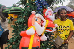 Streetside African Christmas Scene. A woman poses with a Christmas tree and two blowup Santas for sale on the roadside in Accra, Ghana Royalty Free Stock Image