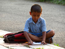 Streetside Study. A little Indian boy sits down on a roadside footpath to study before his exam Royalty Free Stock Photos
