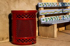 Streetside Trash Can. A painted bus stop bench with a really cool looking red trash can next to it Royalty Free Stock Photography