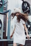 Cute girl dancing in white dress and fur hat in city Stock Photos