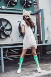 Girl in white dress, green socks and fur hat. Streetstyle, fashion. Girl in white dress, green socks and fur hat. Propellers on background Stock Images