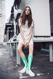 Teenager in white dress and socks on the street. Streetstyle, fashion. Teenager in white dress and socks on the street. Propellers on background Royalty Free Stock Photo