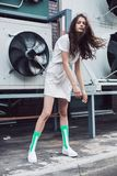 Young girl posing in white dress and green socks on the street. Streetstyle, fashion. Young girl posing in white dress and green socks on the street. Propellers Stock Photos